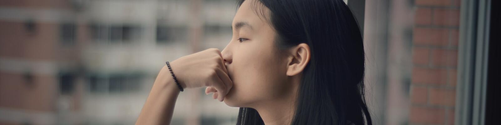 vrouw kijkt uit peinzend uit het raam